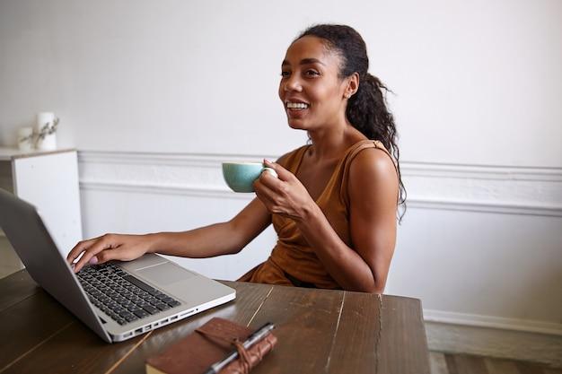Portret van vrolijke donkere vrouw met kopje koffie in haar hand zittend aan een houten tafel, werken met haar laptop, in een goede bui