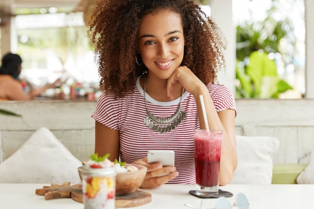 Portret van vrolijke donkere vrouw met kroeshaar, blogs in netwerken op slimme telefoon, heeft dinerpauze, eet exotische schotel in café, verbonden met snel internet. vrouw stuurt berichten