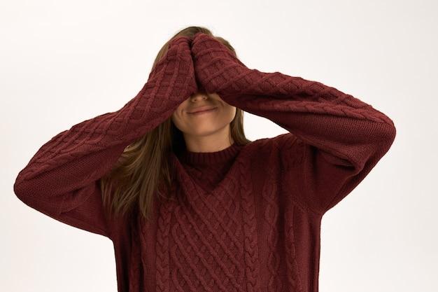 Portret van vrolijke donkerharige jonge vrouw poseren geïsoleerd in kastanjebruine gebreide trui met plezier verstoppertje spelen, ogen bedekken met beide handen, glimlachend.