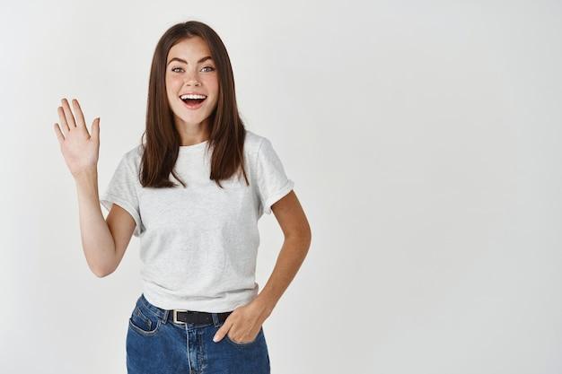 Portret van vrolijke europese vrouw in t-shirt, zwaaiend met de hand in hallo gebaar en breed glimlachend, witte muur.
