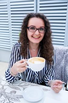 Portret van vrolijke europese vrouwelijke manager met ontbijtpauze aan tafel op caféterras, glimlachende freelancer-vrouw die met laptop in restaurant koffie drinkt