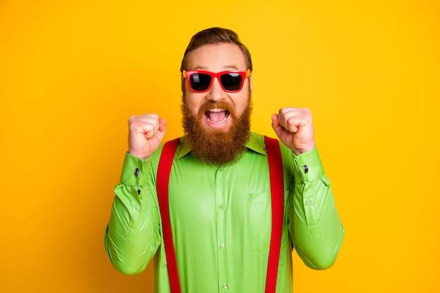Portret van vrolijke extatische man wint prachtige geluksloterij, vuisten, schreeuwen, ja draag er goed uitzien moderne outfit geïsoleerd over felle kleur