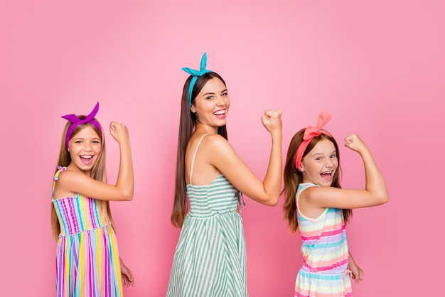 Portret van vrolijke familie die hun vuisten opheft die ja celrbrating overwinning schreeuwen die heldere kledingrok dragen die over roze achtergrond wordt geïsoleerd
