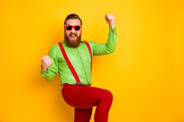 Portret van vrolijke gekke opgetogen man plezier op voorjaarsvakantie winnen wedstrijd loterij vuisten heffen schreeuwen ja draag bretels broek geïsoleerd over gele kleur