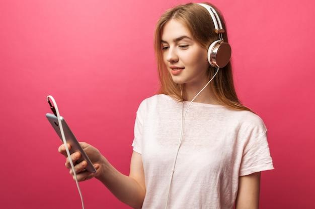 Portret van vrolijke gelukkig meisje luisteren muziek in oortelefoons met leeg scherm van mobiele telefoon