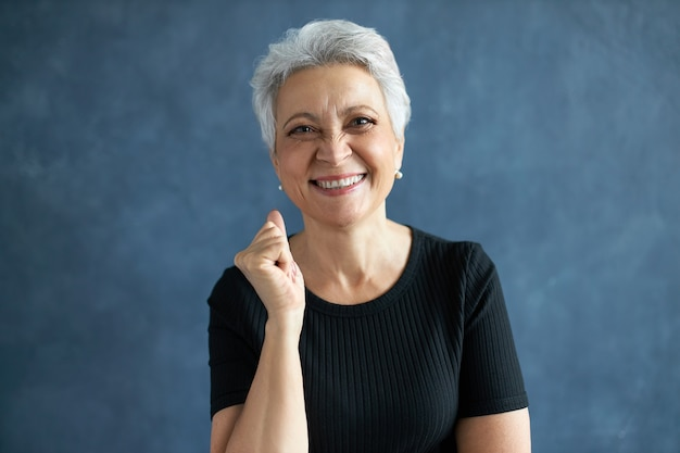 Portret van vrolijke gelukkige blanke vrouw van middelbare leeftijd in zwart t-shirt balde vuist en breed glimlachend.