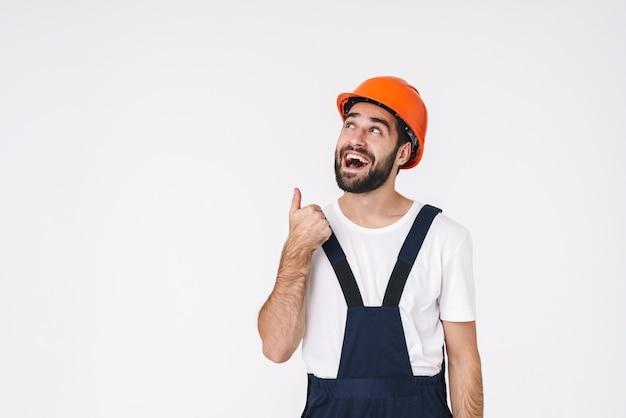 Portret van vrolijke gelukkige jonge man bouwer in helm poseren geïsoleerd over witte muur opzij wijzend.