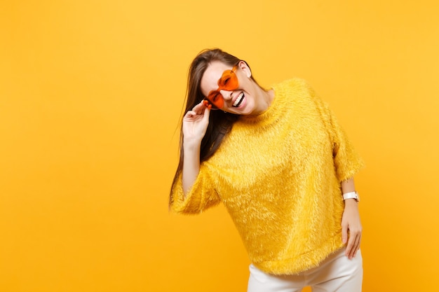 Portret van vrolijke gelukkige jonge vrouw in bont trui, witte broek met hart oranje bril staan geïsoleerd op felgele achtergrond. mensen oprechte emoties, lifestyle concept. reclame gebied.