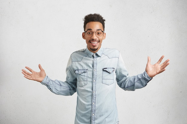 Portret van vrolijke gelukkige man met trendy kapsel, gebaren als blij om positief nieuws te horen.