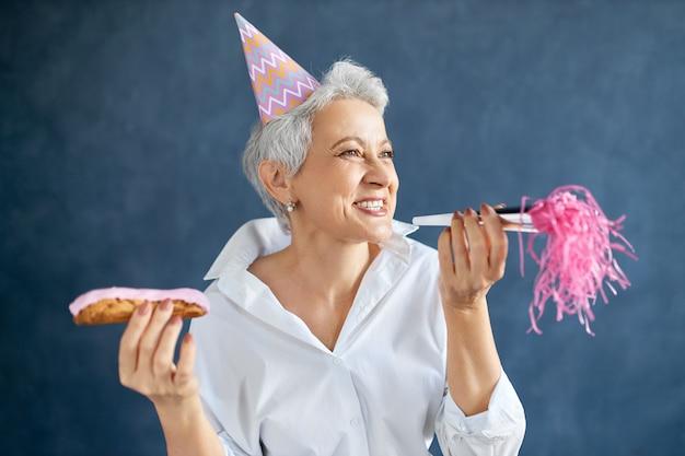 Portret van vrolijke gelukkige vrouw van middelbare leeftijd in wit overhemd poseren geïsoleerd met eclair en noisemaker in haar handen, plezier op verjaardagsfeestje