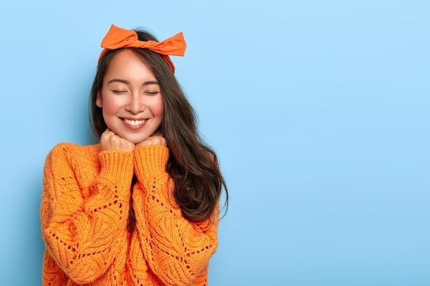 Portret van vrolijke gemengd ras vrouw heeft verlegen tevreden uitdrukking, breed glimlachen, toont witte tanden, draagt oranje boog hoofdband en gebreide trui