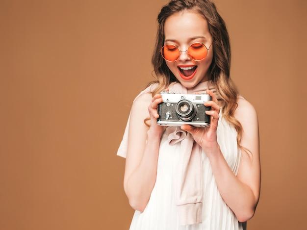 Portret van vrolijke glimlachende jonge vrouw die foto met inspiratie nemen en witte kleding dragen. meisje dat retro camera houdt. model in zonnebril het stellen