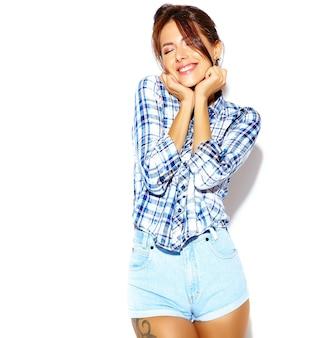 Portret van vrolijke glimlachende mode vrouw gek in casual hipster geruit hemd zonder make-up op witte muur