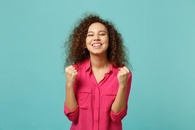 Portret van vrolijke grappige afrikaanse meisje in roze casual kleding winnaar gebaar geïsoleerd op blauwe turquoise muur achtergrond in studio. mensen oprechte emoties, lifestyle concept. bespotten kopie ruimte.
