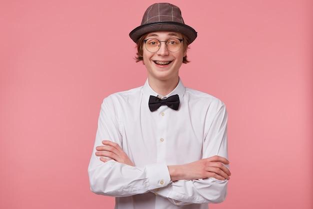 Portret van vrolijke grappige jonge kerel in wit overhemd, hoed en zwarte vlinderdas draagt een bril die gelukkig lachend toont orthodontische beugels, staande met gekruiste handen, geïsoleerd op roze achtergrond