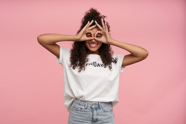Portret van vrolijke grappige krullende brunette dame met donkere huid glazen maken van opgeheven handen terwijl staande op roze, in hoge geest zijn en breed glimlachen