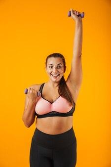 Portret van vrolijke grote sportvrouw in sportieve beha opheffing halters, geïsoleerd op gele achtergrond