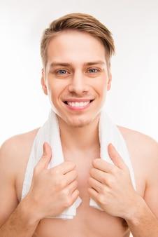 Portret van vrolijke hansome jonge gezonde man met handdoek op zijn nek