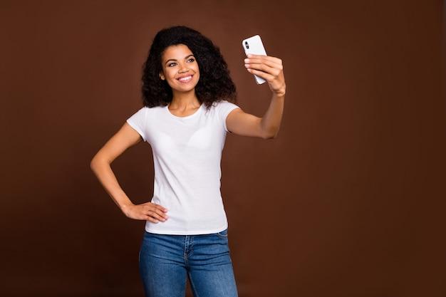 Portret van vrolijke inhoud afro amerikaans meisje geniet van reis, maak selfie op haar smartphone, draag stijlvolle, goed uitziende kleding.