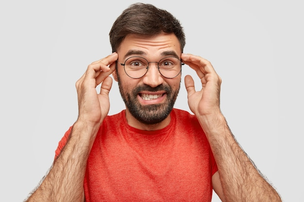 Portret van vrolijke intelligente man toont tanden, houdt de handen op tempels, denkt ergens aan