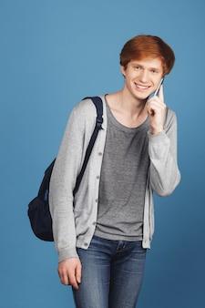 Portret van vrolijke jonge aantrekkelijke studentenkerel met gemberhaar in de toevallige rugzak van de uitrustingsholding, die helder glimlachen, sprekend met vriend op celtelefoon met gelukkige uitdrukking.