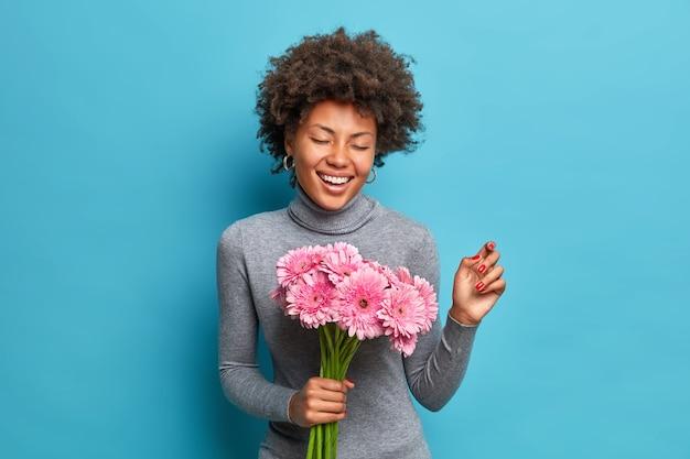 Portret van vrolijke jonge afro-amerikaanse vrouw met krullend haar houdt breed boeket van roze gerbera's glimlacht