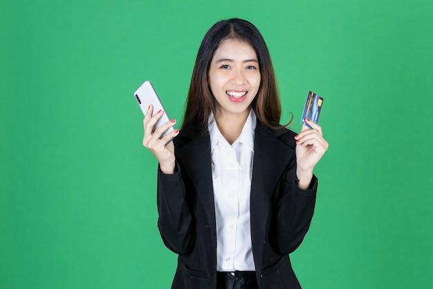Portret van vrolijke jonge aziatische onderneemster die mobiele slimme telefoon en creditcard houdt