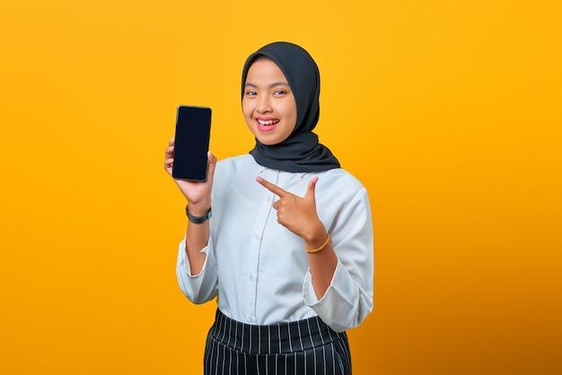 Portret van vrolijke jonge aziatische vrouw die het lege scherm van de smartphone op gele achtergrond toont