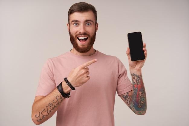 Portret van vrolijke jonge bebaarde brunette man met tattooes met grote ogen en mond geopend en tonen met wijsvinger op zijn smartphone in opgeheven hand, geïsoleerd op wit