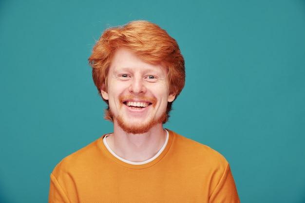 Portret van vrolijke jonge bebaarde man met volle haardos lachend op blauw