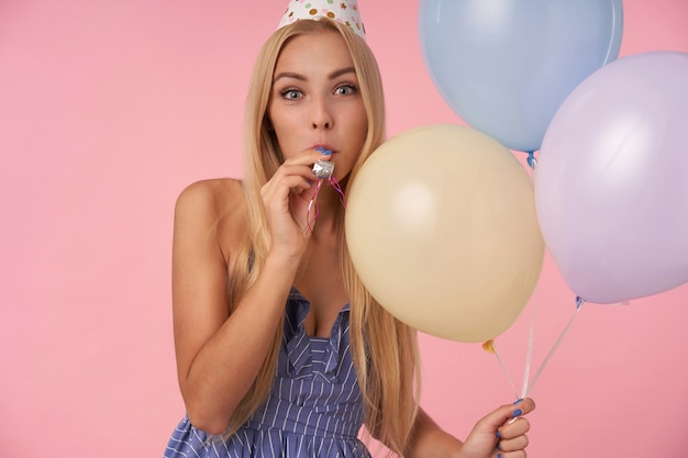 Portret van vrolijke jonge blonde vrouw met lang haar holday outfit dragen en houden van veelkleurige lucht ballonnen, camera vreugdevol kijken en blazen partij hoorn, poseren op roze achtergrond
