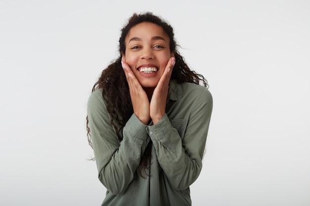 Portret van vrolijke jonge bruinogige donkerharige krullende vrouw met natuurlijke make-up die haar gezicht met opgeheven handpalmen vasthoudt en vrolijk lacht, geïsoleerd op witte achtergrond