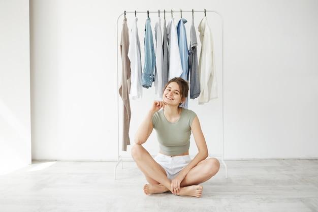 Portret van vrolijke jonge brunette vrouw die lacht zittend op de vloer over hanger kledingkast en witte muur.