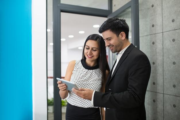 Portret van vrolijke jonge collega's die op digitale tablet doorbladeren