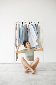 Portret van vrolijke jonge donkerbruine vrouw het glimlachen zitting op vloer onder kleren op hangergarderobe over witte muur.