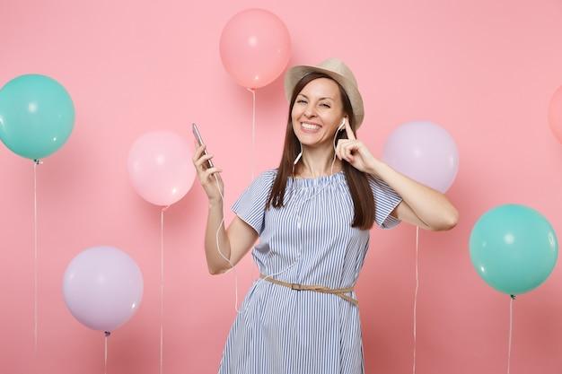 Portret van vrolijke jonge gelukkige vrouw in stro zomer hoed en blauwe jurk met mobiele telefoon en koptelefoon luisteren muziek op roze achtergrond met kleurrijke lucht ballonnen. verjaardagsfeestje concept.