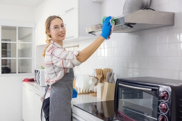 Portret van vrolijke jonge huisvrouw met schoonmaakspullen holding
