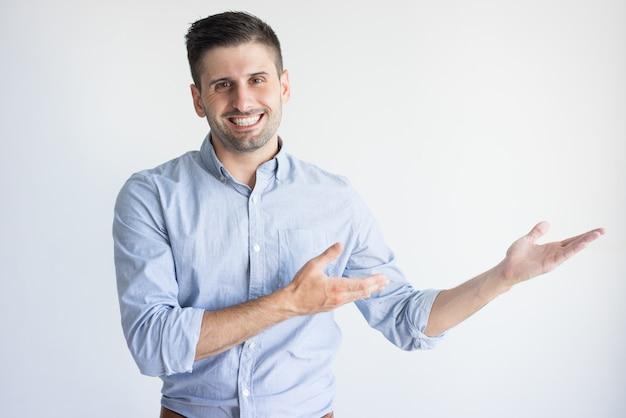 Portret van vrolijke jonge kaukasische manager die product toont.