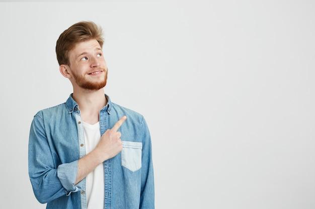 Portret van vrolijke jonge knappe man glimlachend wijzende vinger omhoog.