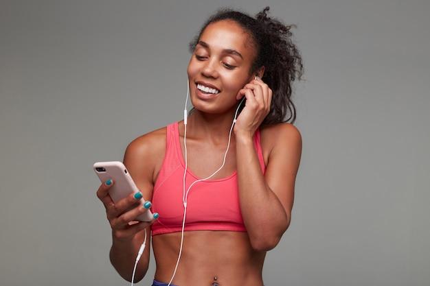 Portret van vrolijke jonge krullende brunette vrouw met donkere huid oortje invoegen in haar oor en breed glimlachen, mobiele telefoon in opgeheven hand houden en positief naar scherm kijken