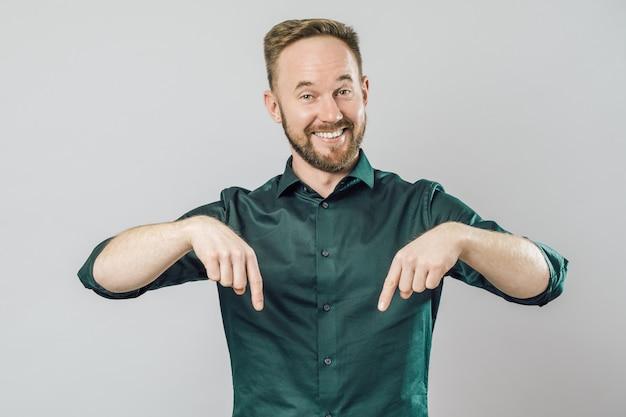 Portret van vrolijke jonge man die wijzende vinger glimlacht