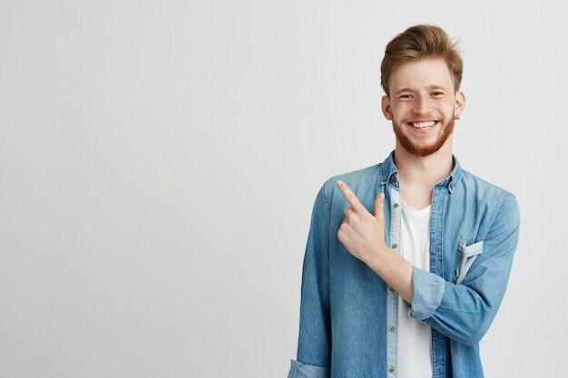 Portret van vrolijke jonge man glimlachend wijzende vinger omhoog.