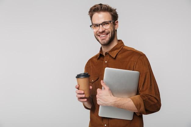 Portret van vrolijke jonge man in bril poseren met laptop en papieren beker geïsoleerd over witte muur