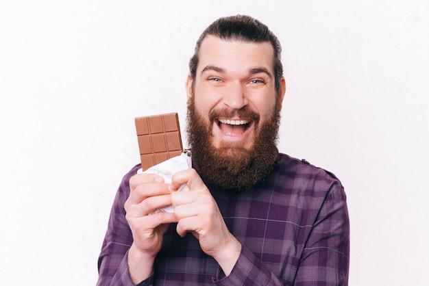 Portret van vrolijke jonge man met baard met blok chocolade