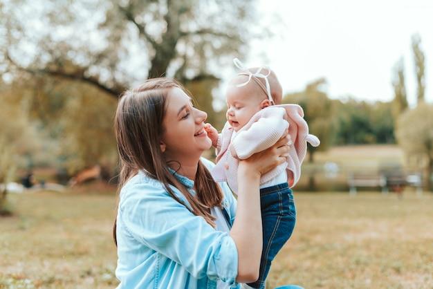 Portret van vrolijke jonge moeder die tijd met haar babymeisje buitenshuis heeft