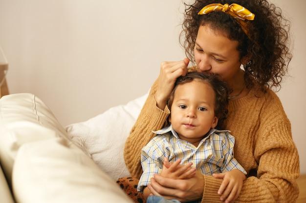 Portret van vrolijke jonge moeder in vrijetijdskleding uiting geven aan al haar liefde en tederheid aan drie-jarige zoontje, hem zachtjes kussen op het voorhoofd, moederschap verlof besteden aan de zorg voor peuter kind