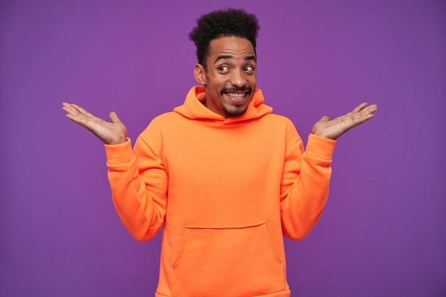 Portret van vrolijke jonge mooie bebaarde donkere man met zwart krullend haar schouderophalend met opgeheven handpalmen en breed glimlachend, gekleed in oranje hoodie terwijl poseren op paars
