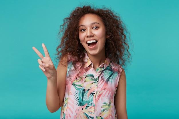Portret van vrolijke jonge mooie bruinharige krullende dame die vredesgebaar toont terwijl ze opgewonden kijkt met geopende mond, geïsoleerd op blauw
