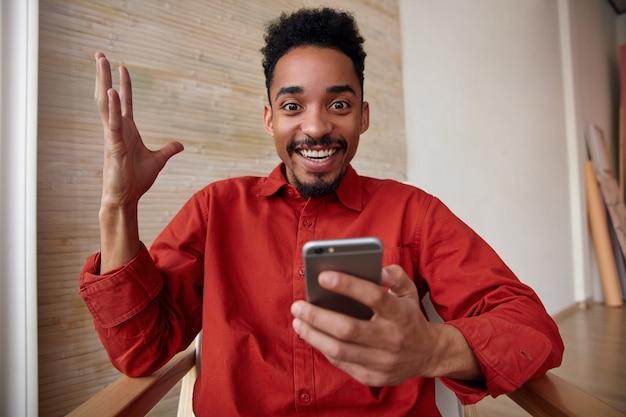 Portret van vrolijke jonge mooie kortharige donkerhuidige man met baard die zijn hand opheft terwijl hij vrolijk kijkt met een brede glimlach, die zich voordeed op interieur