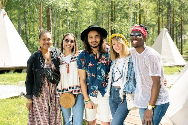 Portret van vrolijke jonge multi-etnische vrienden in hippie-outfits die elkaar omhelzen op festival in boscamping